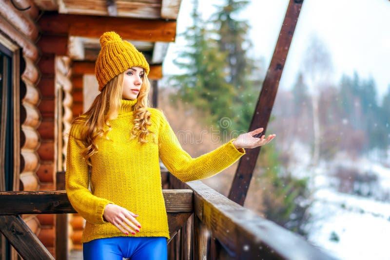 Junges Mädchen in einer Winterstrickjacke, die heraus ihre Hände zum Schnee ausdehnt lizenzfreies stockfoto