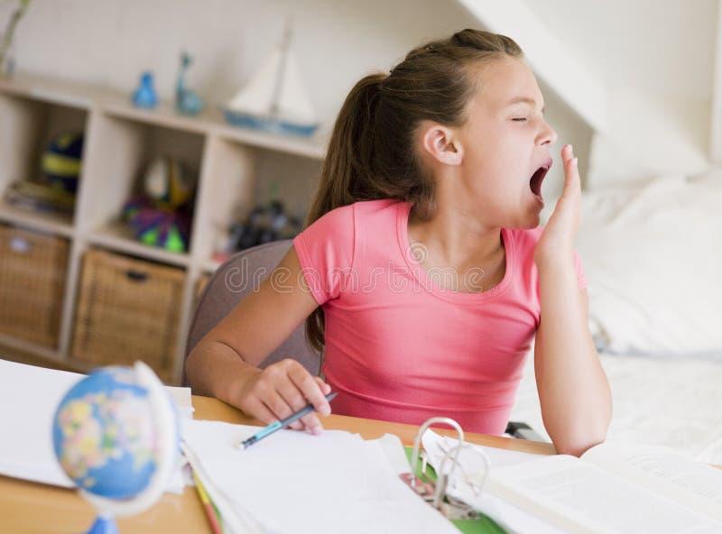 Junges Mädchen-Gähnen, ihre Heimarbeit tuend stockbild