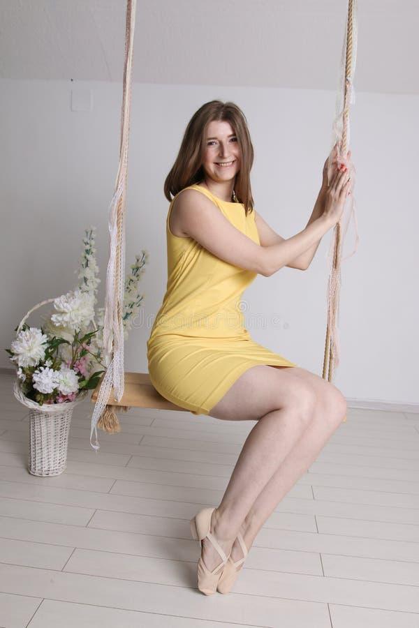 Junges Mädchen im gelben Kleid auf Schwingen in einem Raum stockfoto