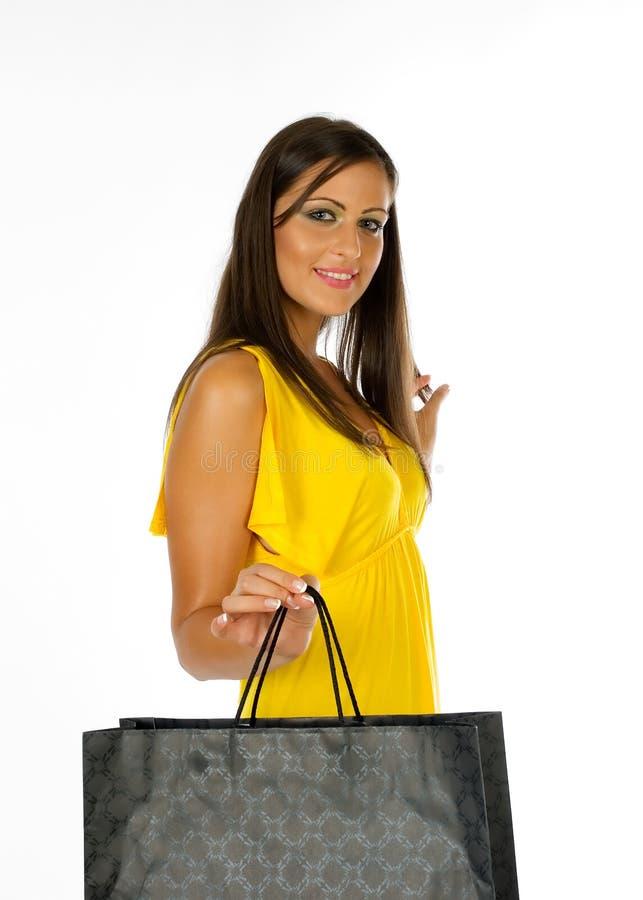 Junges Mädchen im gelben Kleideinkaufen-Holdingbeutel stockbilder