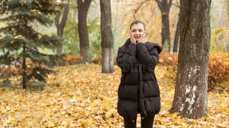 Junges Mädchen im Herbstpark in der schwarzen Jacke stockbilder