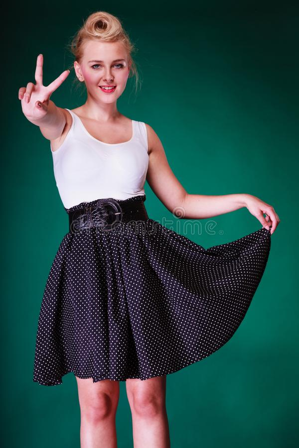 Junges Mädchen im Retro- Kleid, das Frieden zeigt, singen lizenzfreies stockbild