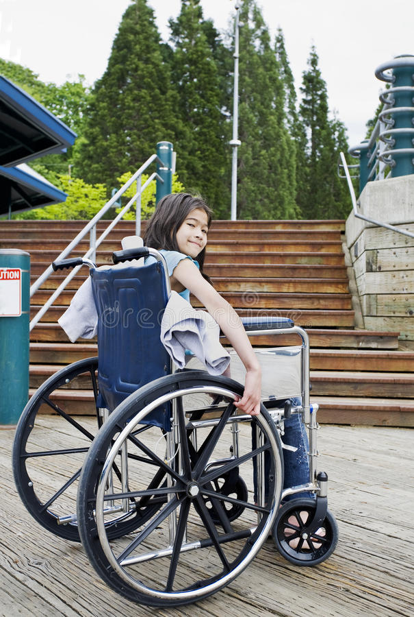 Junges Mädchen im Rollstuhl vor Treppen lizenzfreie stockfotografie