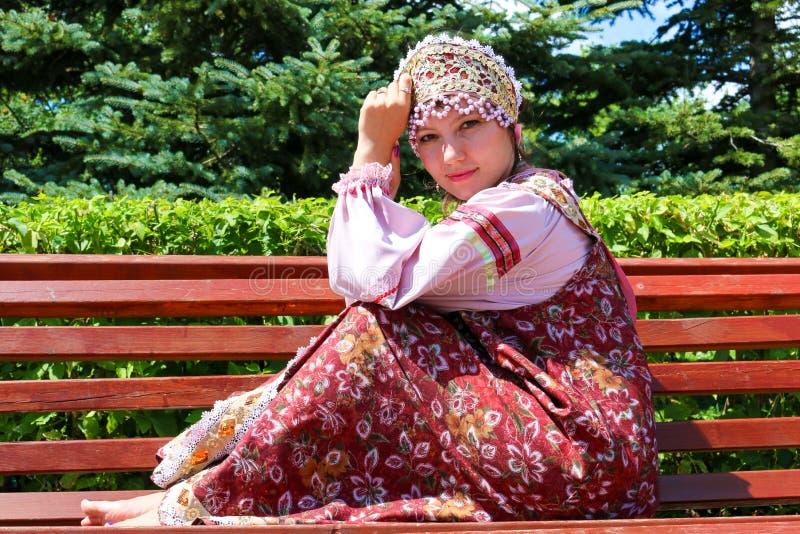 Junges Mädchen im russischen Volkskostüm sitzt auf der Bank stockbilder