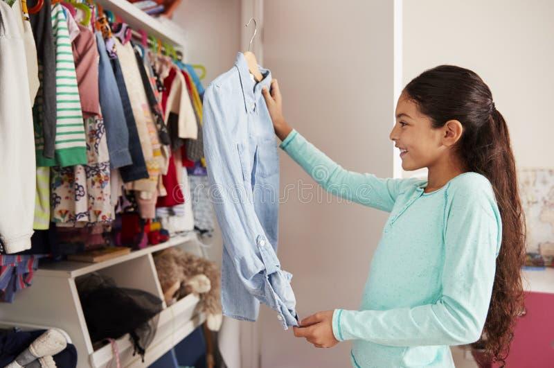 Junges Mädchen im Schlafzimmer, das Kleidung vom Wandschrank wählt lizenzfreie stockfotos