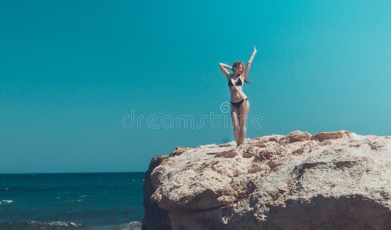 Junges Mädchen im schwarzen Bikini, der am Felsen nahe Meer, Kreta, Griechenland steht stockfotos