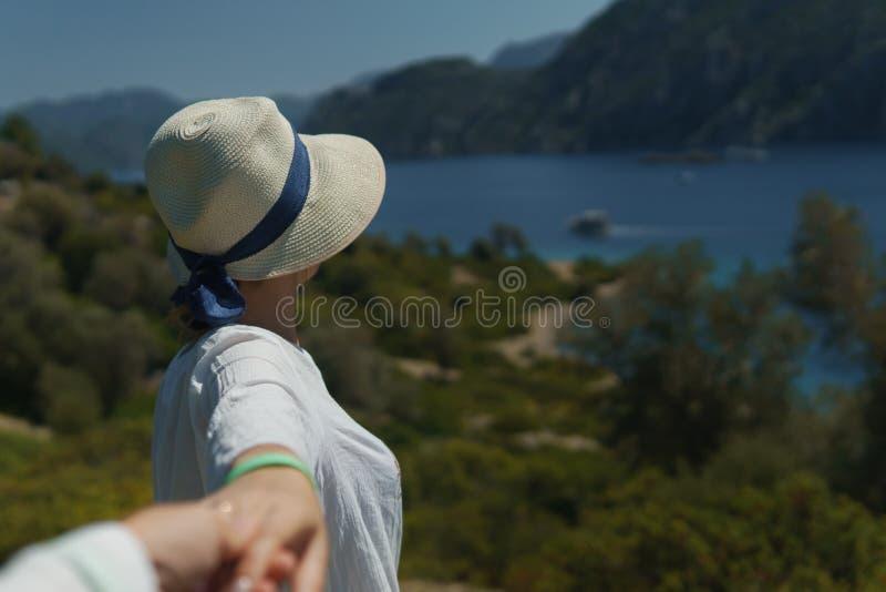 Junges Mädchen im unbekannte Mann ` s eine Hand haltenen und nennenden Hut nachdem er, um die schöne Natur und das Meer zu genieß stockbild