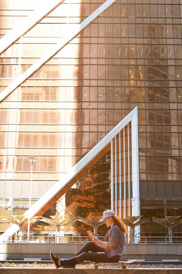 junges Mädchen ist, lesend sitzend und ein Buch auf einem Skateboard in einer Großstadt auf dem Bürgersteig stockfoto