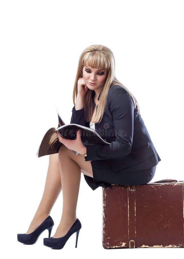 Junges Mädchen kleidete im Anzug an und saß auf Kofferlesung lizenzfreies stockbild