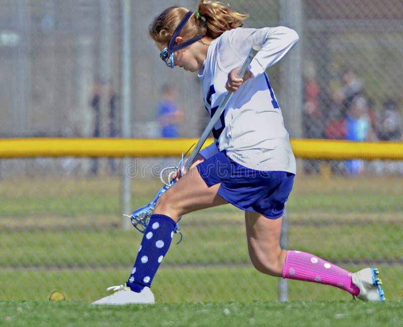 Junges Mädchen Lacrosse-Spieler, der für den Ball läuft lizenzfreies stockbild