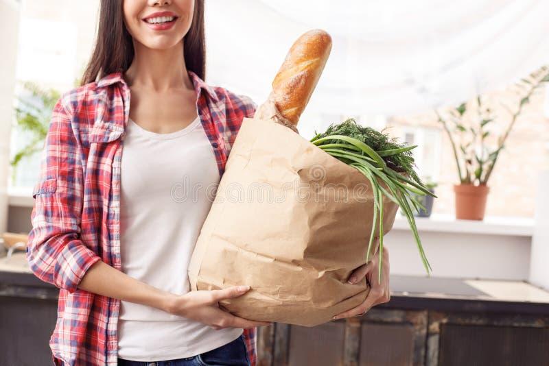 Junges Mädchen Lebensstilstellungs-Holdingtasche der Küche an der gesunden mit Stangenbrot und positiver Nahaufnahme des Gemüses lizenzfreie stockbilder