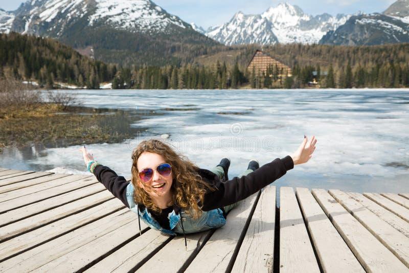 Junges M?dchen liegt durch gefrorenen Gebirgssee Strbske Pleso - vor stockfotografie