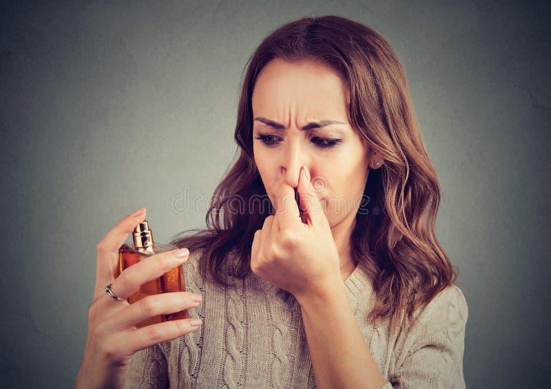 Junges Mädchen missfallen mit Parfüm stockfotografie