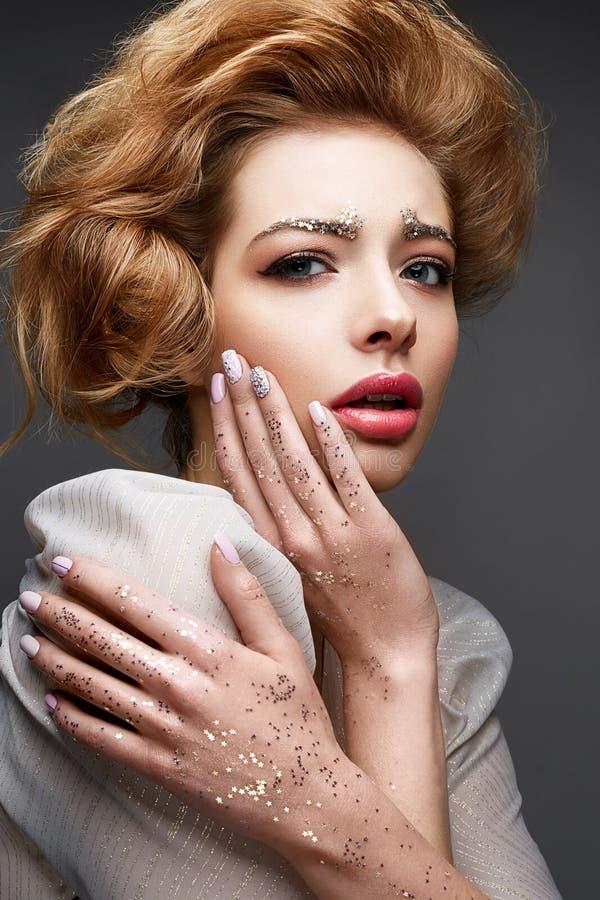 Junges Mädchen mit üppigem Frisur und Make-up Akt Schönes Modell mit Pailletten auf den Augenbrauen und mildern rosa Maniküre lizenzfreies stockbild