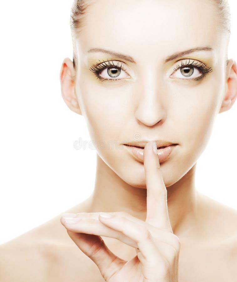 Junges Mädchen mit dem Finger über ihrem Mund lizenzfreies stockbild