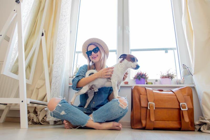 Junges Mädchen mit dem Hund, der nahe bei Koffer sitzt lizenzfreie stockbilder