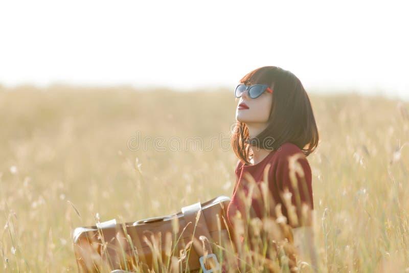 Junges Mädchen mit dem Koffer, der am trockenen Gras sitzt lizenzfreie stockfotografie