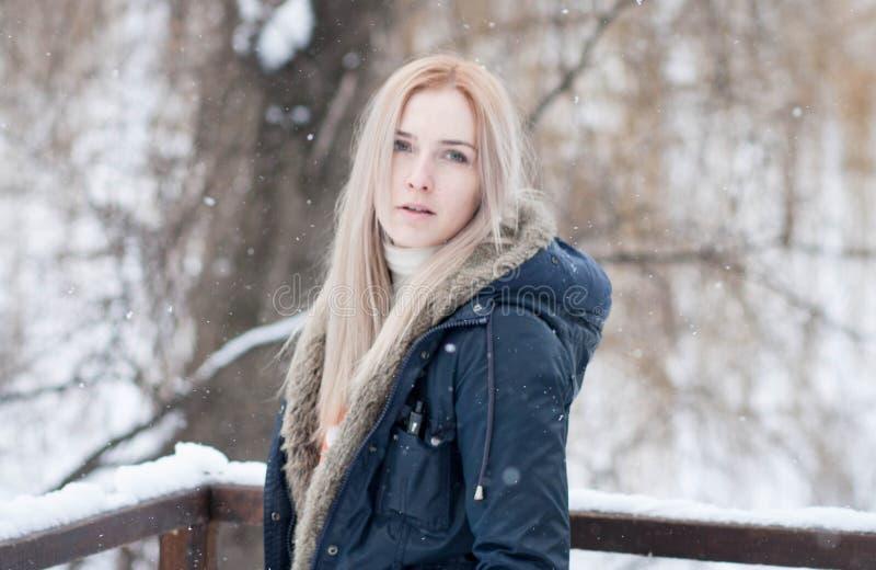 Junges Mädchen mit dem langen blonden Haar auf einem unscharfen Hintergrund eines Parks des verschneiten Winters lizenzfreies stockfoto