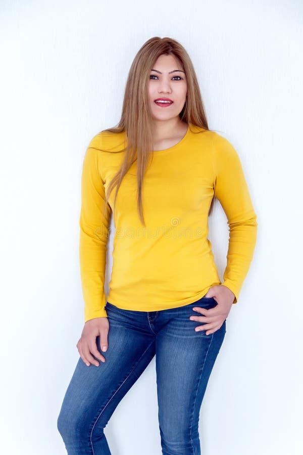 Junges Mädchen mit dem langen braunen gesunden Haar im Gelb lizenzfreie stockfotografie