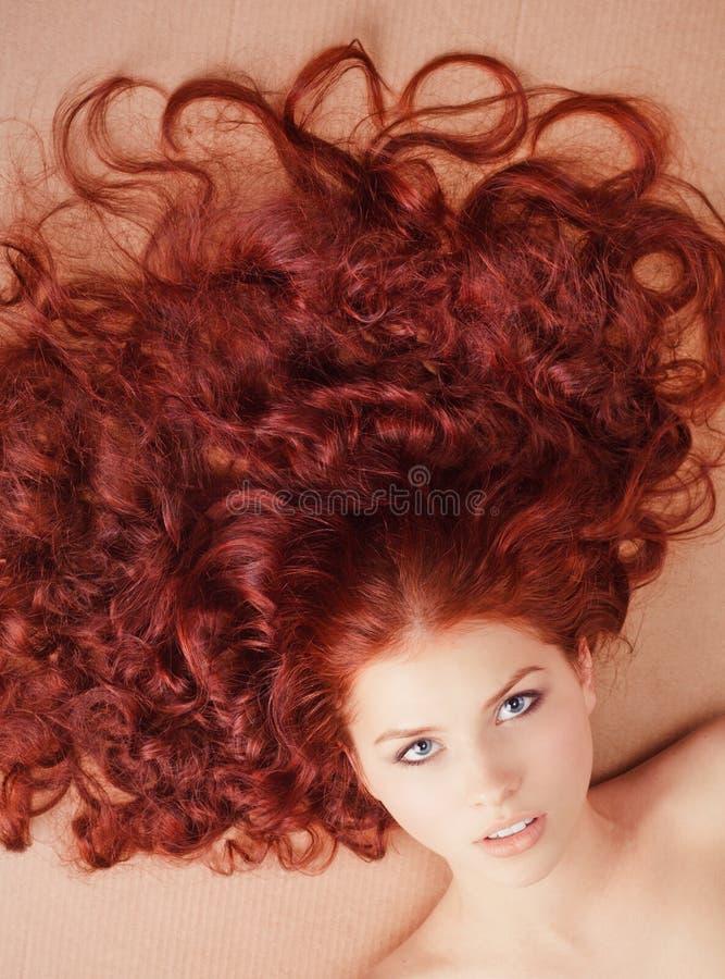 Junges Mädchen mit dem langen Haar, das auf dem Fußboden liegt lizenzfreie stockbilder