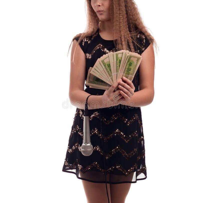 Junges Mädchen mit dem langen Haar, das einen schwarzen Kleider- und Goldhut mit einem Mikrofon in seiner Hand und in Geld auf ei stockfotografie