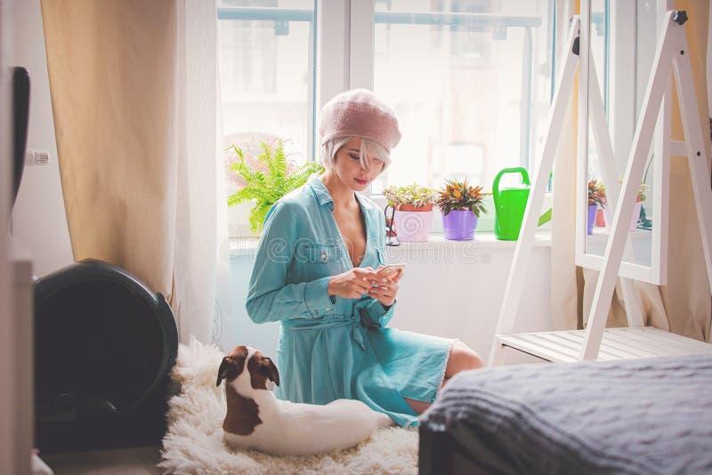 Junges Mädchen mit dem rosa Haar und Barett mit Hund stockfotografie