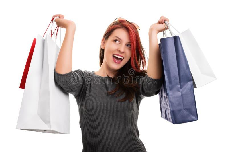 Junges Mädchen mit den Einkaufstaschen lokalisiert auf weißem Hintergrund lizenzfreie stockfotografie