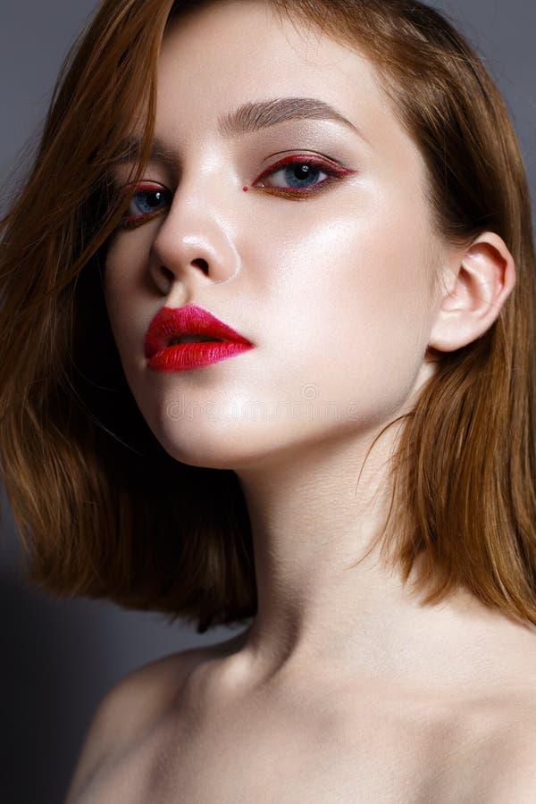 Junges Mädchen mit den roten Lippen und den roten Pfeilen vor Augen Schönes Modell mit Make-upakt und glänzender Haut Foto eingel stockbilder