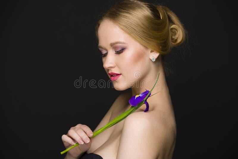 Junges Mädchen mit den Veilchen, die auf einem Schwarzen, nahtloser Hintergrund aufwerfen lizenzfreie stockfotografie