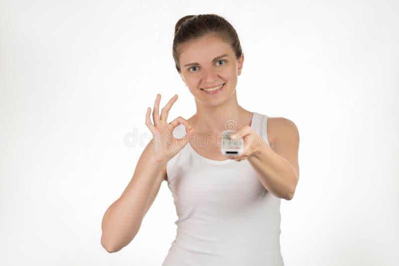 Junges Mädchen mit der Fernbedienung, die auf die Knöpfe, lächelnd drückt und stockbilder