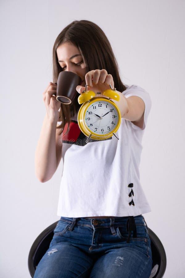 Junges Mädchen mit der Retro- Uhr in der Hand, die Zeit zeigt und den Kaffee lokalisiert auf weißem Hintergrund trinkt lizenzfreie stockfotos