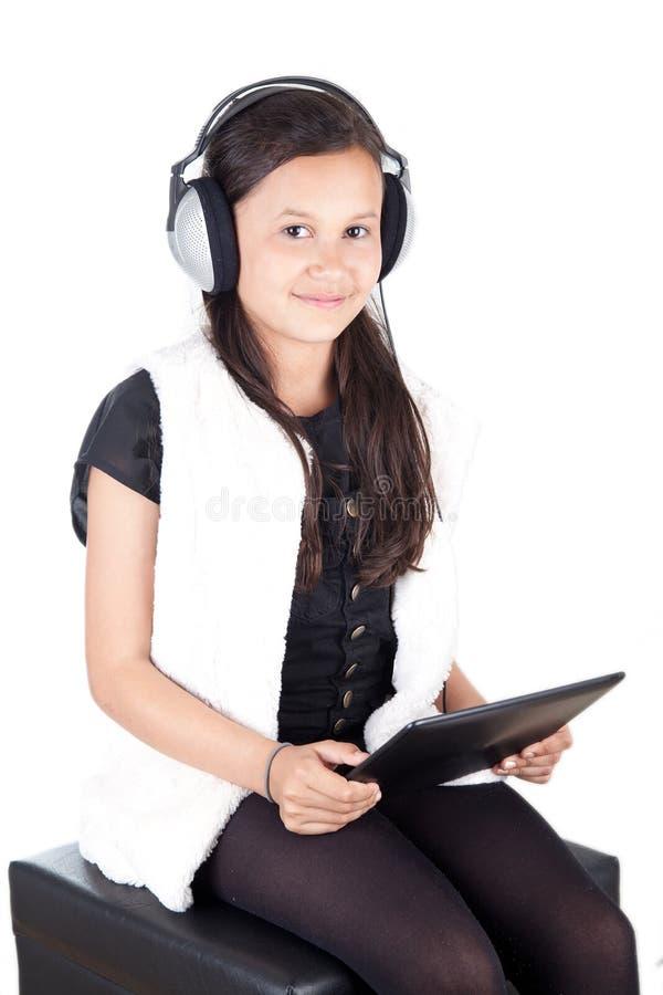 Junges Mädchen mit digitaler Tablette und Kopfhörern lizenzfreie stockbilder