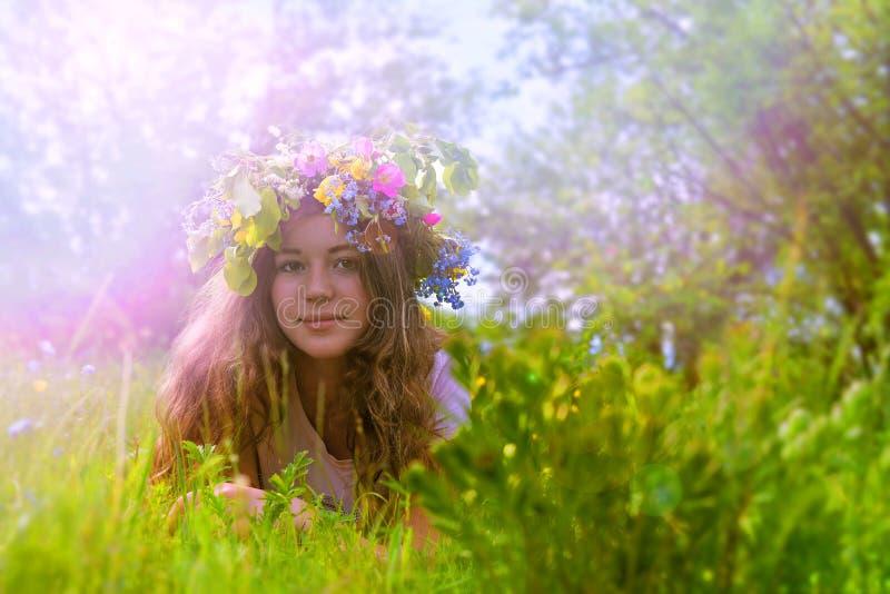 Junges Mädchen mit einem Blumenkranz auf ihrem Kopf auf dem Gras stockbild