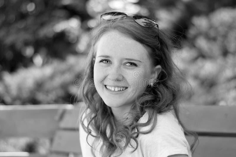 Junges Mädchen mit einem Lächeln auf der Bank lizenzfreie stockfotografie