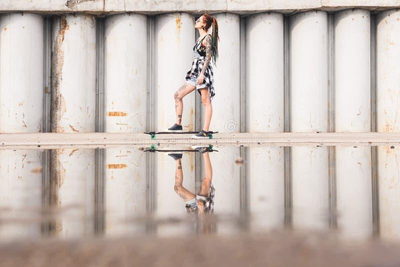 Junges Mädchen mit einem longboard auf dem Hintergrund der Betonkonstruktion lizenzfreies stockbild
