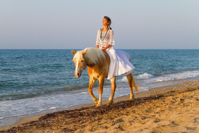 Junges Mädchen mit einem Pferd auf dem Strand stockfotografie