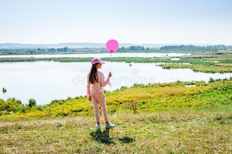 Junges Mädchen mit einem rosa Ball auf dem See beim Gehen in das nationale stockfoto