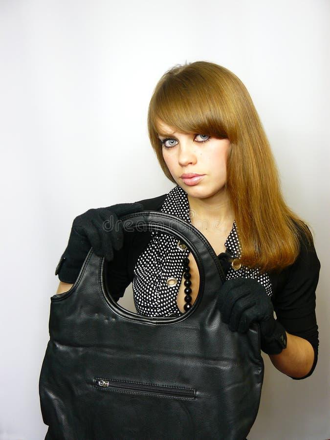Junges Mädchen mit einem schwarzen ledernen Beutel stockfoto