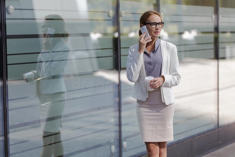 Junges Mädchen mit einem Smartphone und einem Tasse Kaffee steht auf Stadtstraße nahe bei Geschäftszentrum lizenzfreie stockfotografie