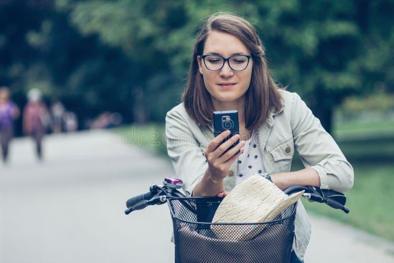 Junges Mädchen mit Fahrrad unter Verwendung des intelligenten Telefons stockbilder