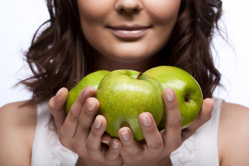 Junges Mädchen mit frischen drei grünen Äpfeln lizenzfreie stockfotos