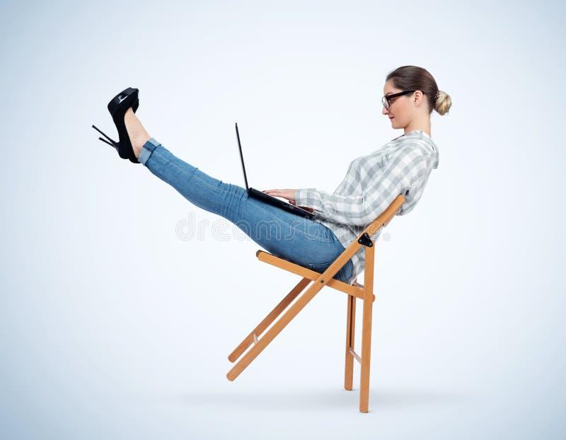 Junges Mädchen mit Gläsern balanciert auf einem Holzstuhl, der an einem Laptop, Konzept des Entspannung bei der Arbeit arbeitet stockbilder