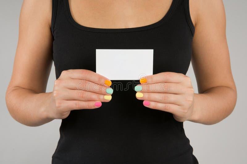 Junges Mädchen mit heller Maniküre führt Visitenkarte vor lizenzfreie stockbilder