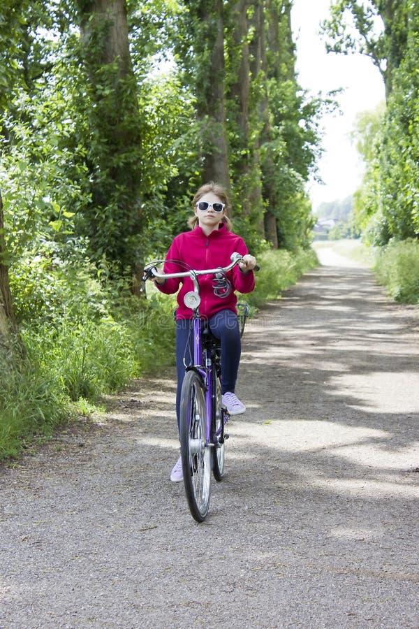 Junges Mädchen mit ihrem Fahrrad lizenzfreie stockfotos