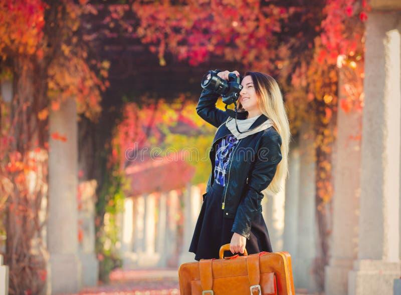 Junges Mädchen mit Koffer und Kamera in der Gasse der roten Trauben lizenzfreie stockfotos