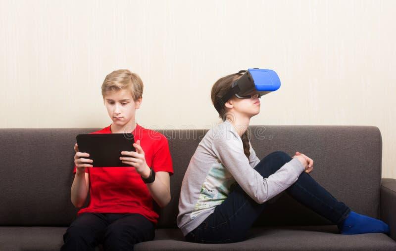Junges Mädchen mit Kopfhörer und Jungen der virtuellen Realität mit der Tablette, die zu Hause auf Sofa sitzt lizenzfreie stockbilder