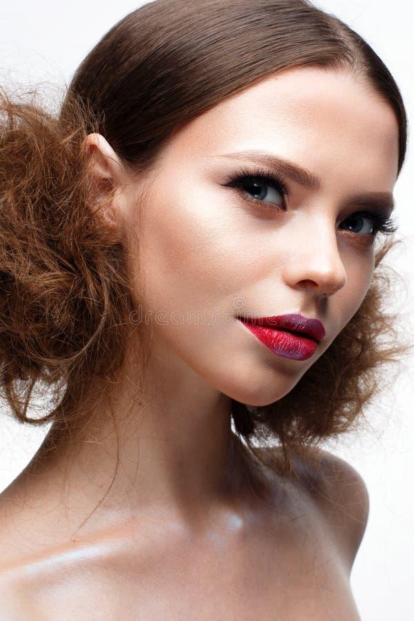 Junges Mädchen mit kreativem hellem Make-up und glänzender Haut Schönes Modell mit einer Frisur, Pfeile auf Augen und Rotlippen S stockfotografie