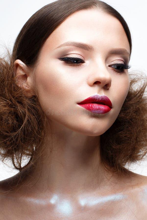 Junges Mädchen mit kreativem hellem Make-up und glänzender Haut Schönes Modell mit einer Frisur, Pfeile auf Augen und Rotlippen S lizenzfreie stockfotografie