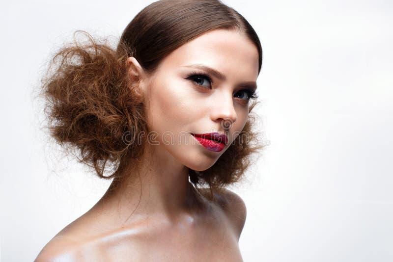 Junges Mädchen mit kreativem hellem Make-up und glänzender Haut Schönes Modell mit einer Frisur, Pfeile auf Augen und Rotlippen S stockbild