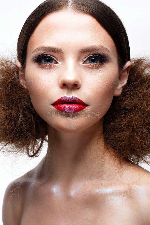 Junges Mädchen mit kreativem hellem Make-up und glänzender Haut Schönes Modell mit einer Frisur, Pfeile auf Augen und Rotlippen S lizenzfreies stockbild